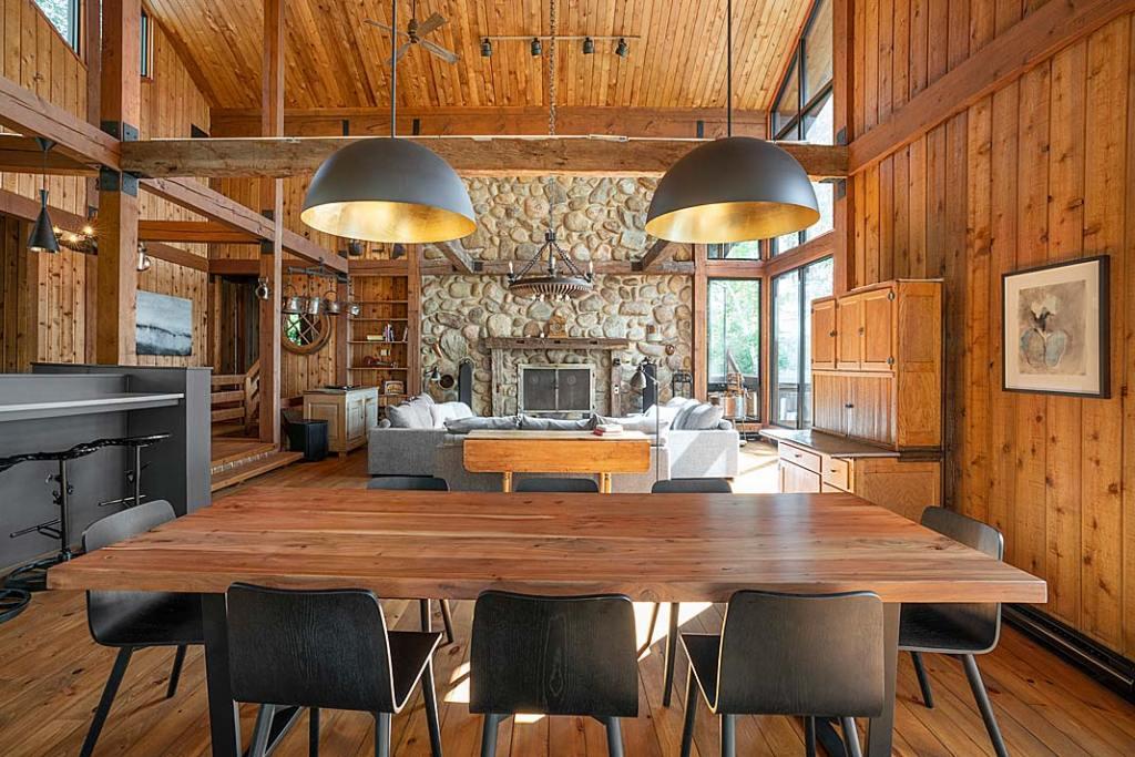 Główna dekoracja salonu: kamienna obudowa kominka, drewniany sufit i odkryte belki