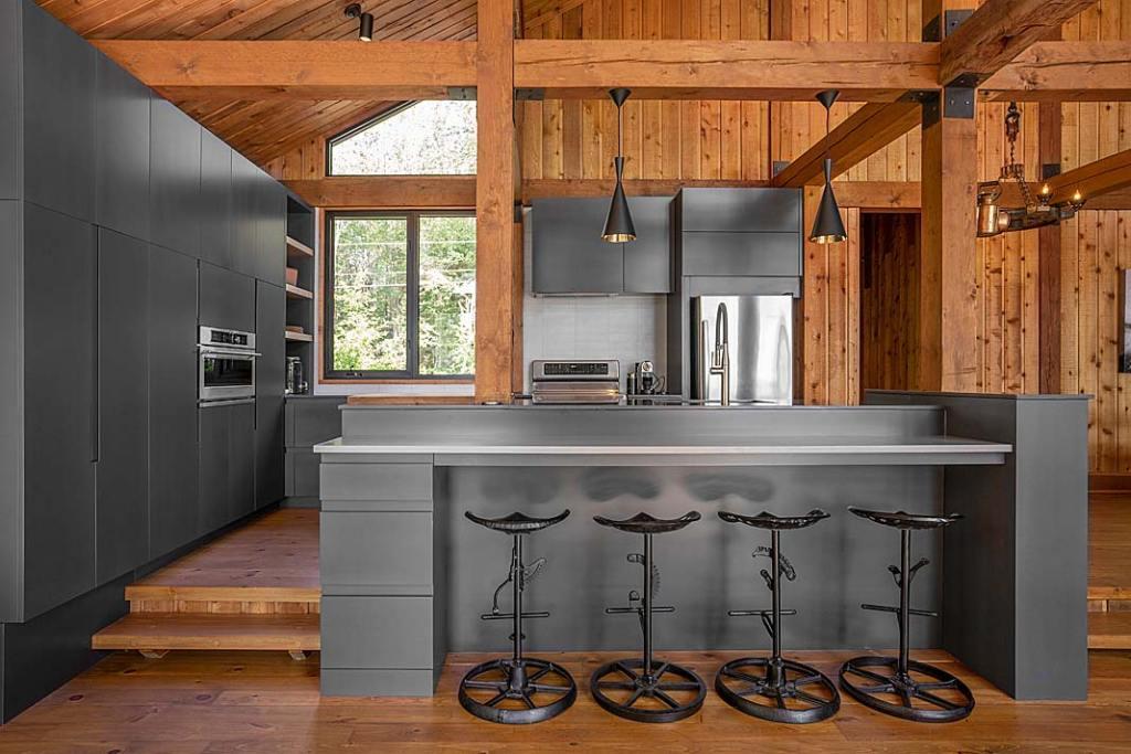 Nowoczesny dom drewniany. Kuchnia z wyspą, szare meble i drewno