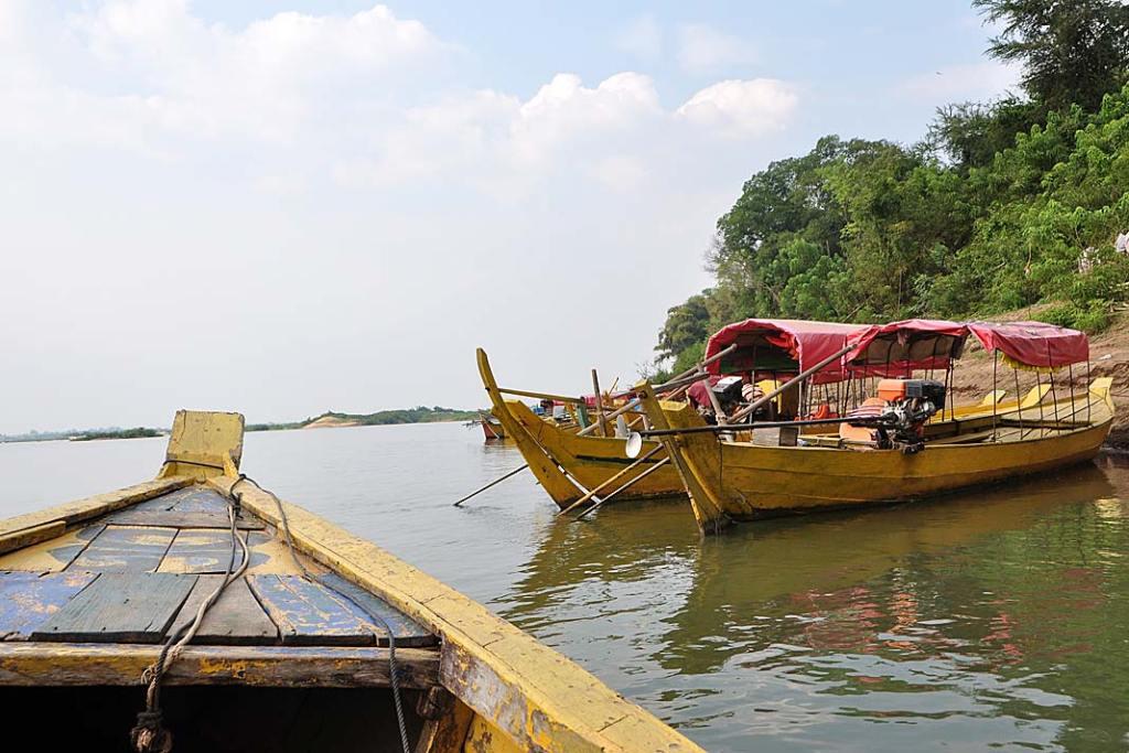 Łodzie przycumowane dobrzegu Mekongu czekają na turystów chcących zobaczyć oreczki krótkogłowe