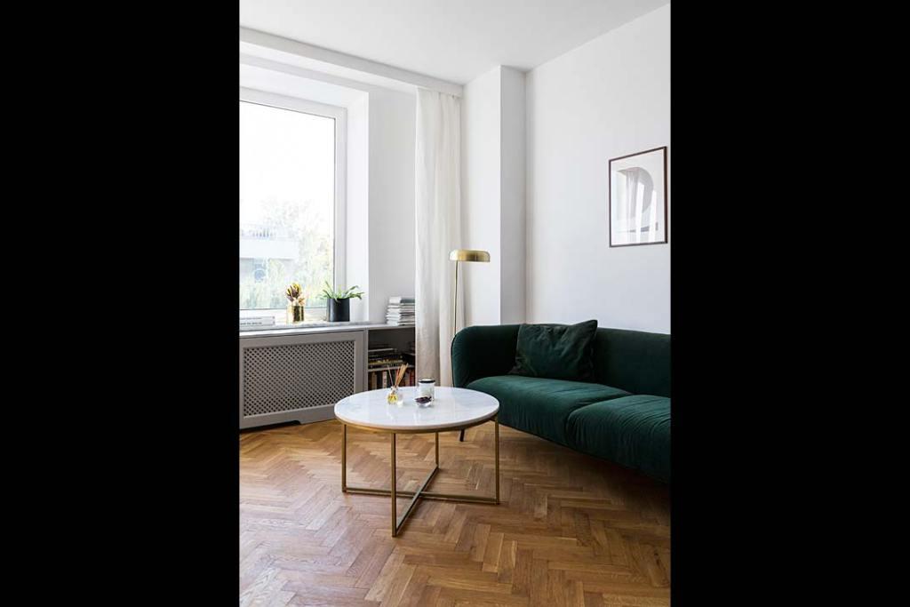 Mieszkanie w modernistycznej kamienicy - welurowa kanapa w kolorze butelkowej zieleni w salonie. Projekt: Magda Milejska i FROPT