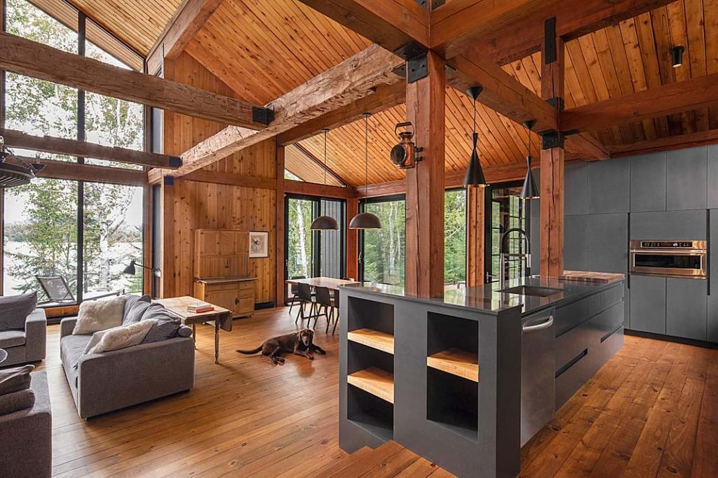 Nowoczesny dom drewniany. Otwarta strefa dzienna łączy kuchnię, jadalnię i salon wykończone drewnem
