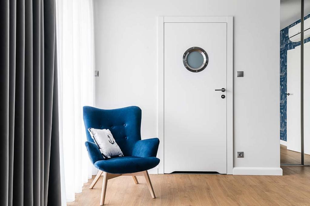 Wnętrza z żeglarskim klimatem - do łazienek prowadzą charakterystyczne drzwi z bulajem. Projekt: Estera i Robert Sosnowscy. Fot. Fotomohito