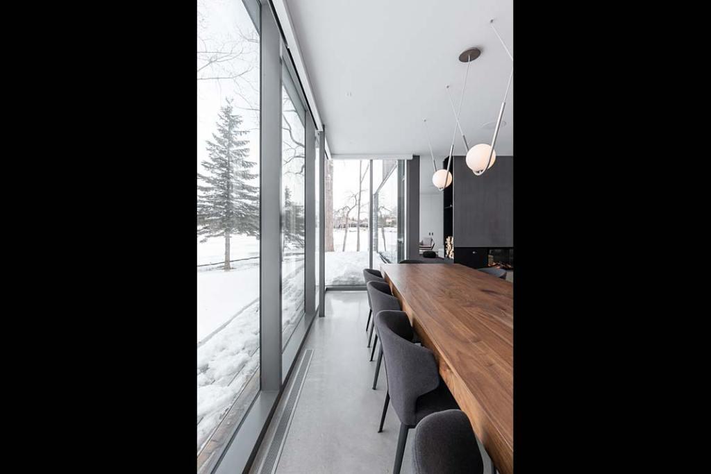 Jadalnia z dużym drewnianym stołem i panoramicznymi oknami
