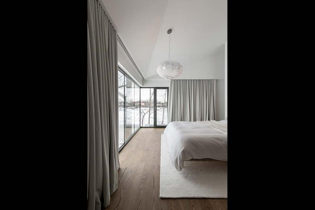 Jasna sypialnia w kolorach ziemi w domu nad jeziorem