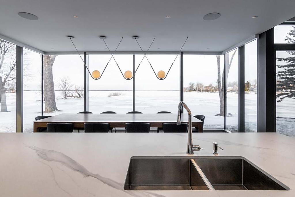 Otwarta kuchnia połączona z jadalnią w domu nad jeziorem