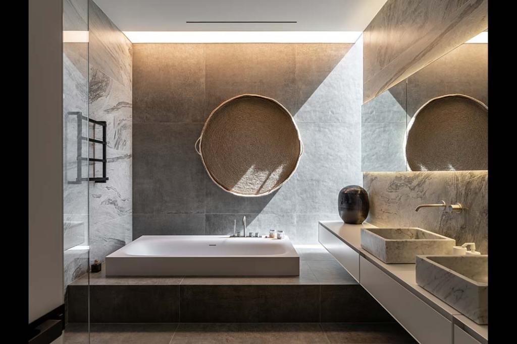 Salon kąpielowy z wanną wpuszczaną w posadzkę i kamienną umywalką