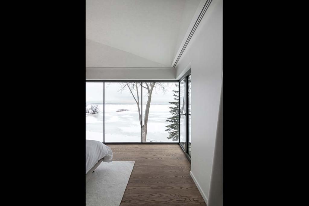 Sypialnia z pięknym widokiem na jezioro dzięki panoramicznym oknom