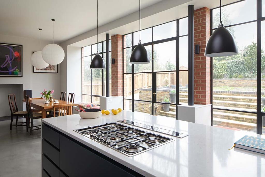 Eklektyczny styl wnętrza zabytkowej willi w Londynie: duże okna ze szprosami podkreślają industrialny charakter części dziennej