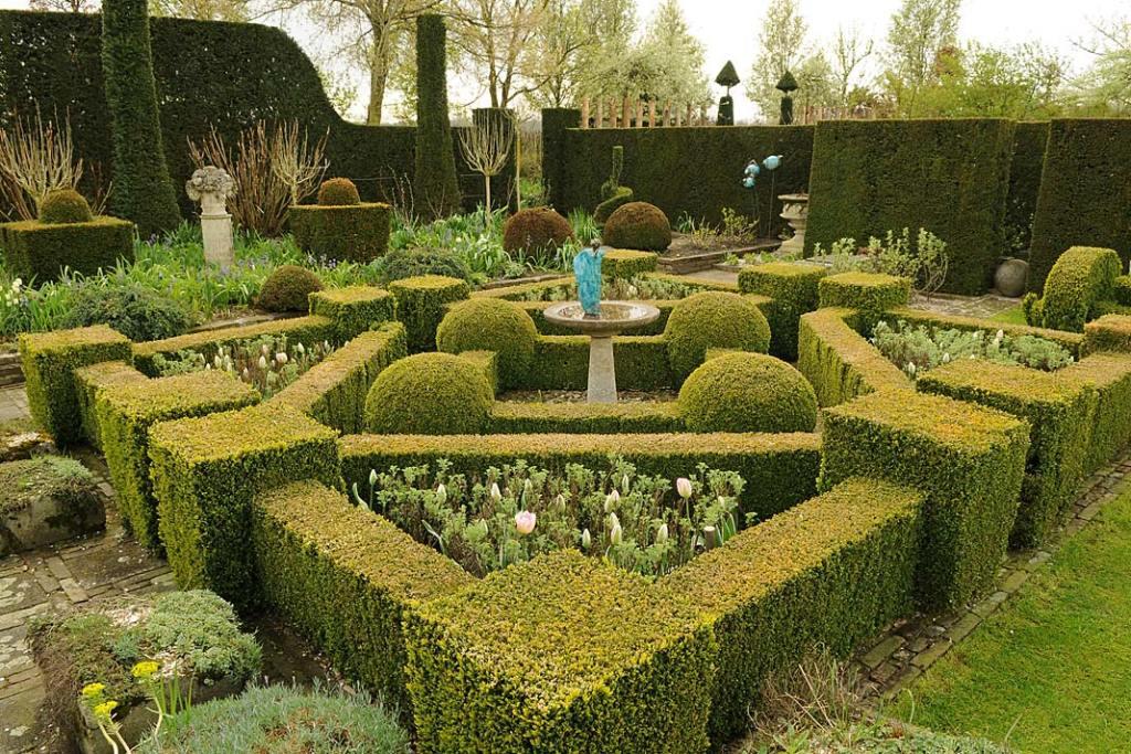 Labirynt ścieżek i bukszpanowych żywopłotów w ogrodzie z fontanną