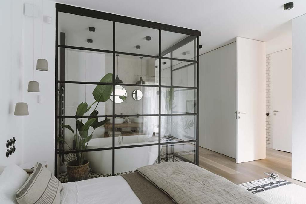 Łazienka oddzielona od sypialni szklaną ścianką z czarnymi szprosami