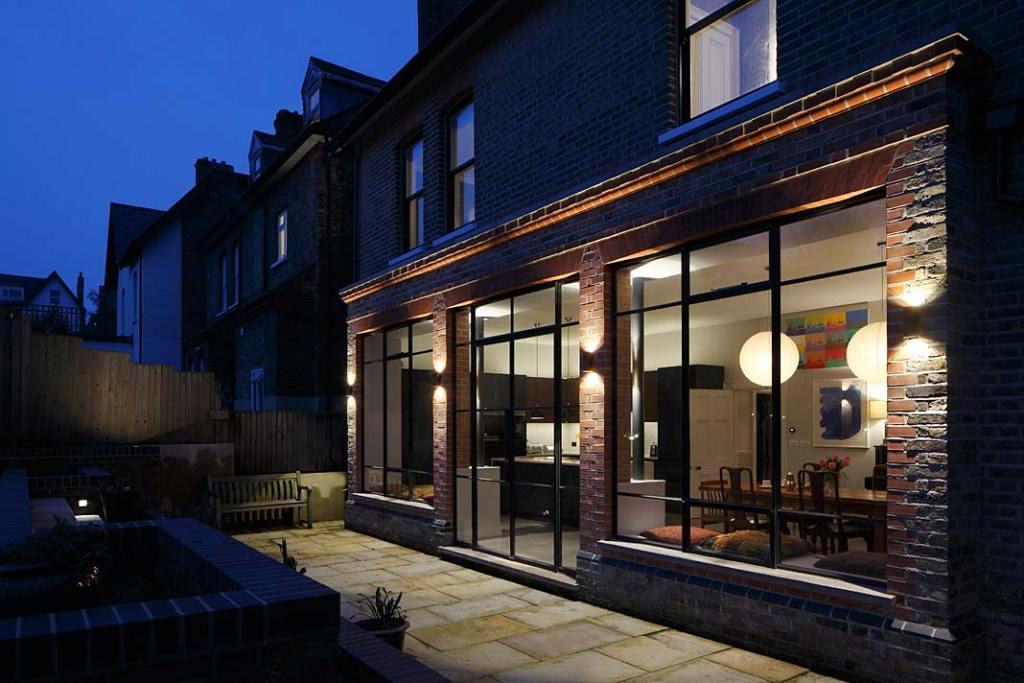 Eklektyczny styl londyńskiej willi - duże okna i nastrojowe oświetlenie po zmroku od strony podwórza