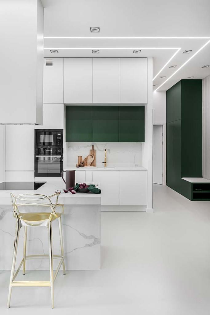 Proste białe szafki kuchenne połączono z frontami w kolorze butelkowej zieleni. Projekt Magdalena Bigos-Smoszna, Idea by Mag