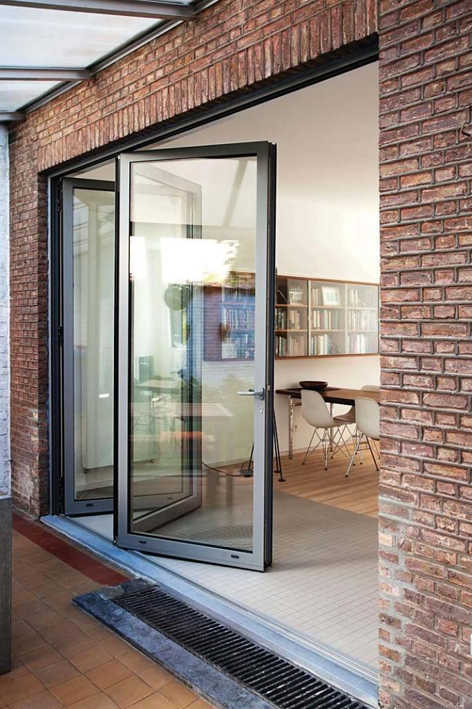 Przesuwne okna tarasowe Reynaers otwierają kuchnię na ogród. Projekt Ardies Lernout Architecten