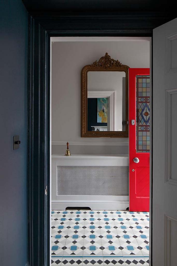 Eklektyczny styl wnętrza zabytkowej willi w Londynie: czerwone drzwi wejściowe zdobione witrażem.