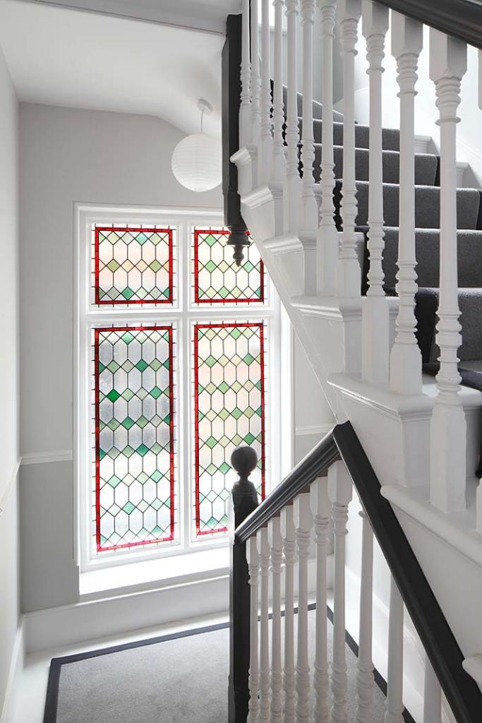 Eklektyczny styl wnętrza zabytkowej willi w Londynie: witraże zdobiące okna klatki schodowej