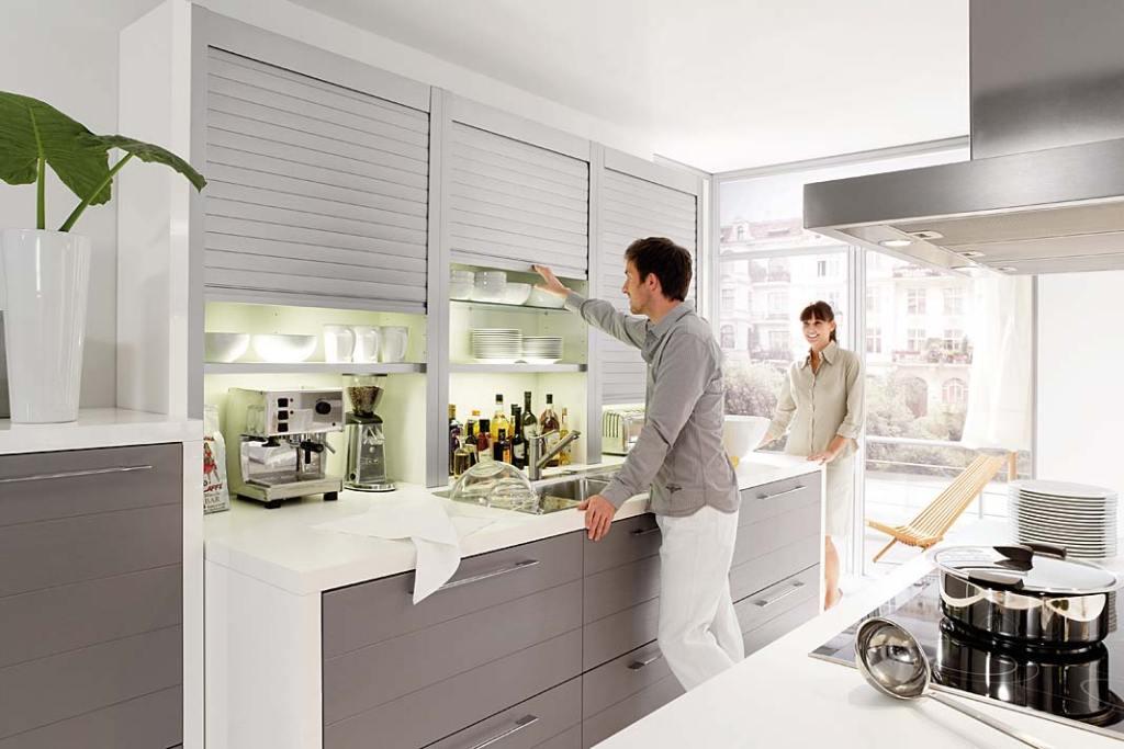 Domowa spiżarnia ukryta za żaluzjowymi drzwiami szafki, propozycja Nolte Kuchen