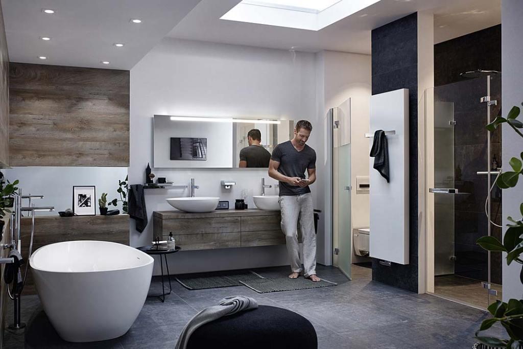 Łazienka z toaletą oddzieloną szklanymi wahadłowymi drzwiami. Aranżacja marki Kermi