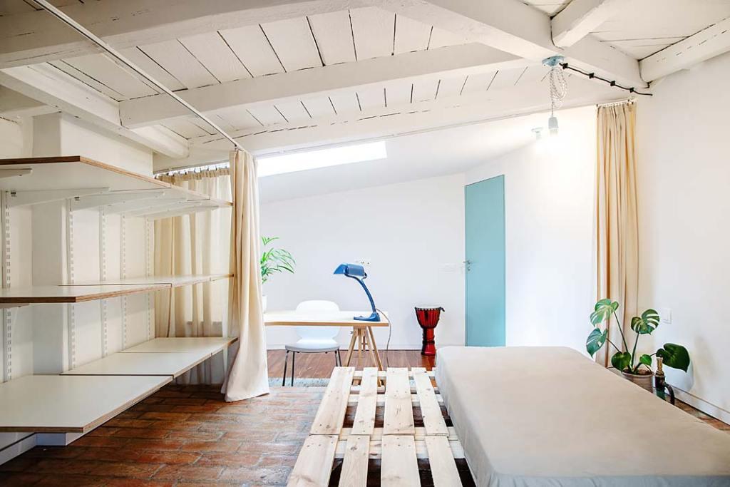 Łóżko z palet i półki z płyt drewnopochodnych wydzielone kotarami. Projekt Atelier Starzak Strebicki