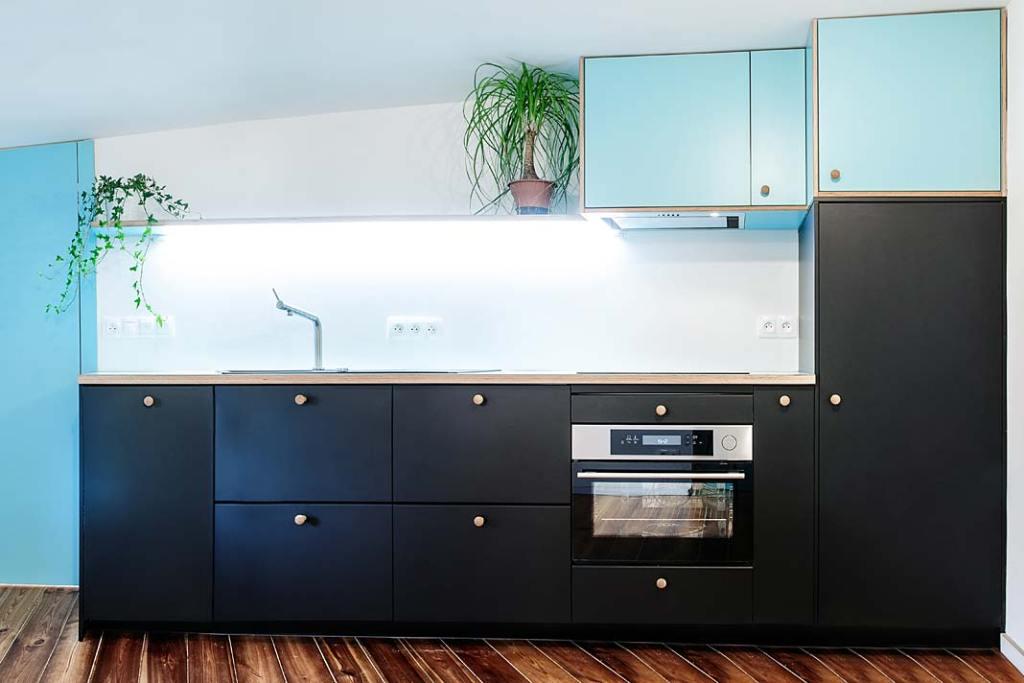 Mieszkanie na strychu, granatowe szafki w kuchni. Projekt Atelier Starzak Strebicki