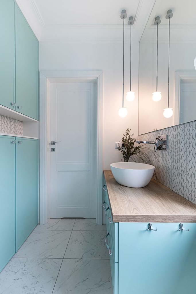Miętowe szafki w gościnnej łazience. Projekt Kowalczyk-Gajda Studio Projektowe