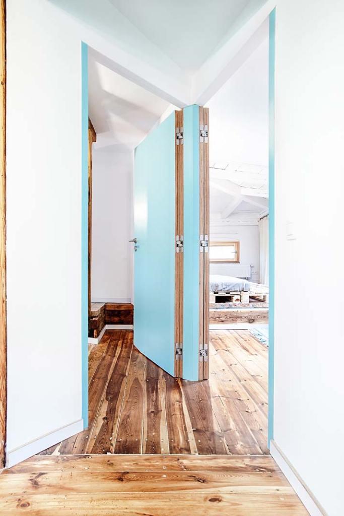 Niebieskie drzwi prowadzą z kuchni do pozostałych pomieszczeń. Projekt Atelier Starzak Strebicki