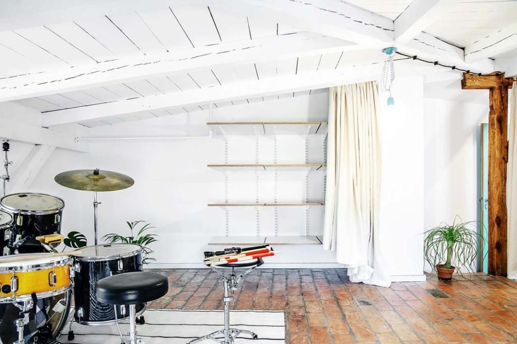 Studio muzyczne w mieszkaniu na strychu, za kotarą przestrzeń do przechowywania. Projekt Atelier Starzak Strebicki