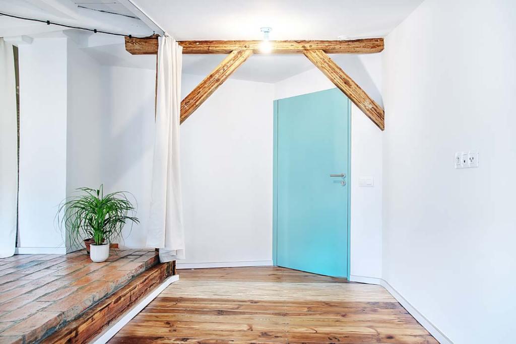 W mieszkaniu na poddaszu zachowano elementy odkrytej więźby dachowej. Projekt Atelier Starzak Strebicki