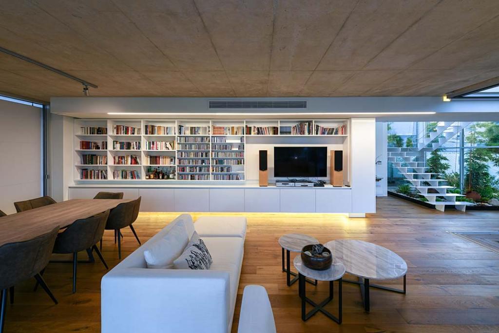 Garden House, dekoracyjne oświetlenie biblioteki w salonie. Projekt Christos Pavlou Architecture