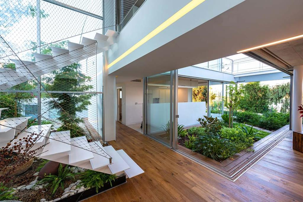 Dom w symbiozie z ogrodem. Garden House, przeszklone pation wewnątrz rezydencji. Projekt Christos Pavlou Architecture