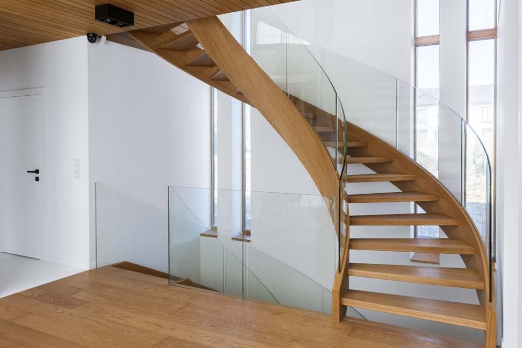 Gięte dębowe schody o konstrukcji policzkowej, szklana balustrada. Projekt i realizacja Schody Trąbczyński
