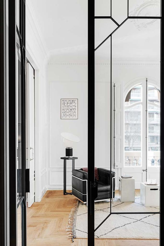 Apartament w Barcelonie, duże przeszklenia w czarnych ramach pełnią funkcję ruchomych ścianek działowych. Projekt Valgreen Studio