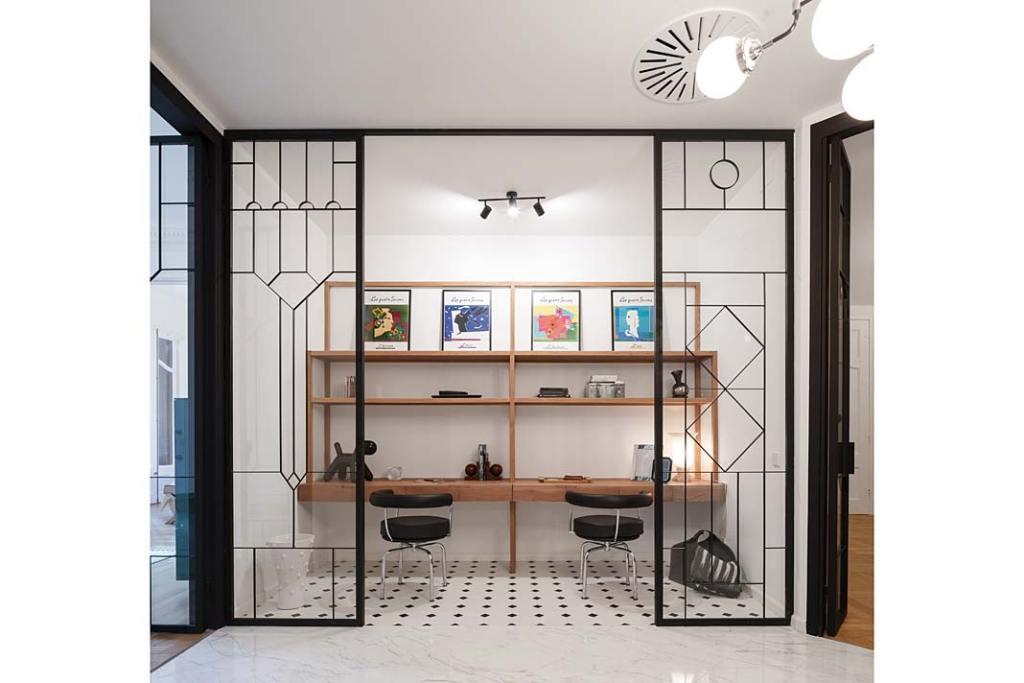 Apartament w Barcelonie, pokój do pracy oddzielono witrażowymi przeszkleniami w czarnych ramach. Projekt Valgreen Studio