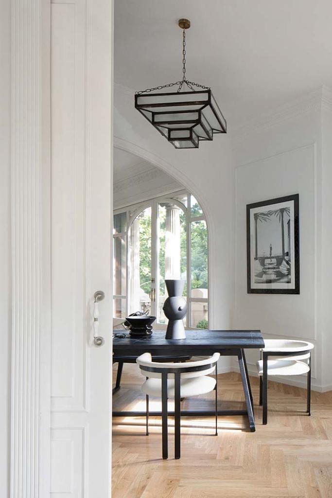 Apartament w Barcelonie, przesuwne drzwi w stylu klasycznym dzielą przestrzeń salonu. Projekt Valgreen Studio