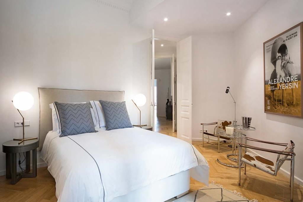 Apartament w Barcelonie, ściany sypialni zdobią plakaty. Projekt Valgreen Studio