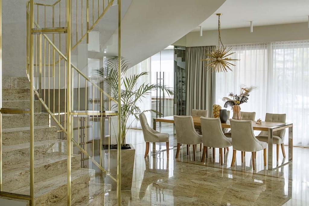 Nowoczesne wnętrza z nutą glamour. Eleganckie schody ze szklaną balustradą w mosiężnej ramie. Projekt Hola Design