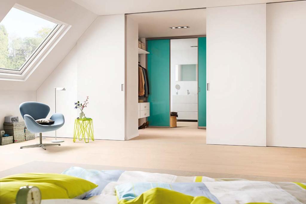 Poddasze użytkowe - sypialnia z garderobą. Aranżacja z drzwiami przesuwnymi Wooden Door marki Raumplus