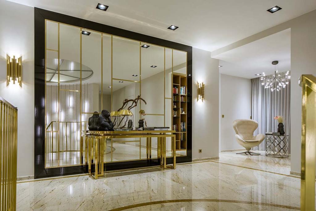 Lustrzana ściana z mosięznymi listwami na piętrze domu. Projekt Hola Design