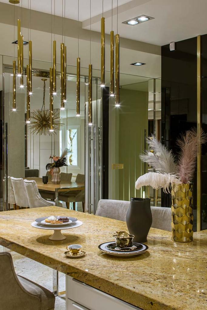 Nad kuchenną wyspą umieszczono złotą lampę Organic z oferty MAXlight. Projekt Hola Design