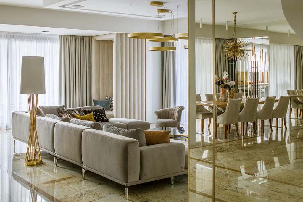 Nowoczesne wnętrza z nutą glamour. Przestrzeń dzienna utrzymana w odcieniach szarości i beżu, ze złotymi dodatkami. Projekt Hola Design