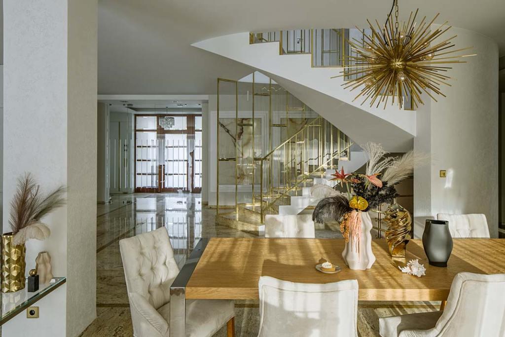 Reprezentacyjna jadalnia z drewnianym stołem i tapicerowanymi krzesłami. Projekt Hola Design