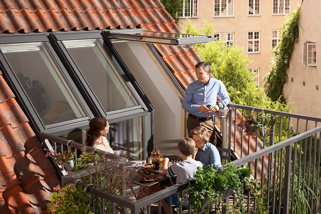 Salon na poddaszu otwarty na balkon, aranżacja z oknami Velux
