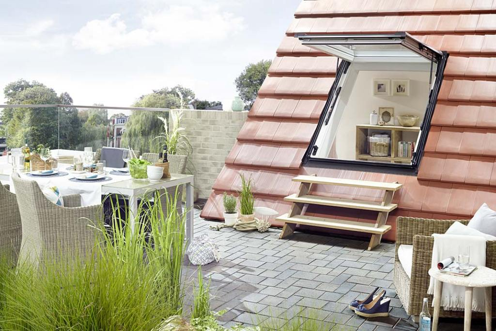 Salon na poddaszu otwarty na balkon, aranżacja z oknem dachowym Designo R8 firmy ROTO