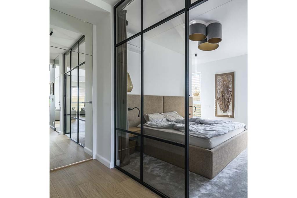 Sypialnię od korytarza oddziela szklana ściana z modnymi czarnymi szprosami. Projekt Plan 9 Studio Architektury