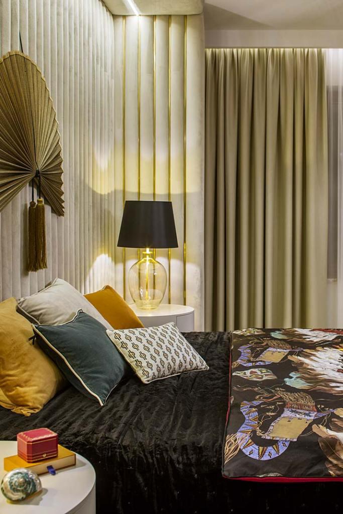 Tapicerowana ściana poprzecinana złotymi listwami tworzy zagłówek łóżka. Projekt Hola Design
