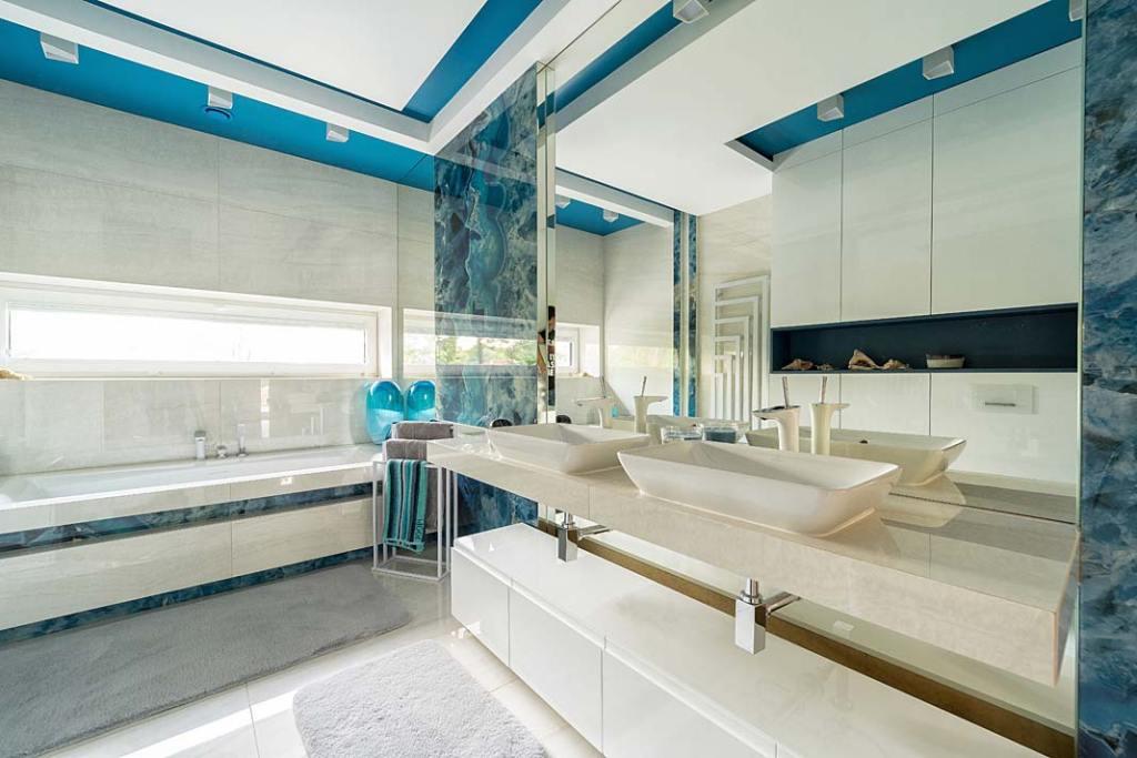 Błękitno-biała łazienka wykończona spiekiem. Projekt Trędowska Design. Fot. Michał Bachulski