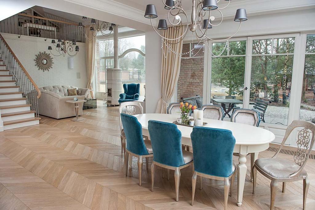 Wielkoformatowe okna, ogrzewanie podłogowe i jodełka francuska Finishparkiet na podłodze w salonie
