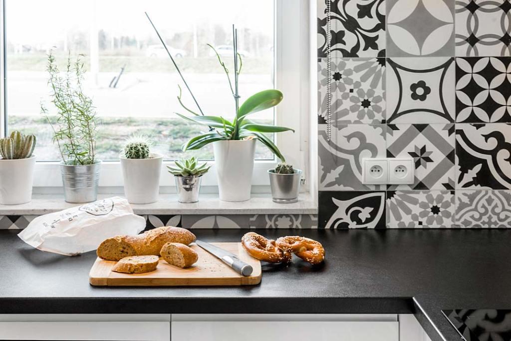 Czarno-biała kuchnia, na ścianie płytki typu patchwork. Projekt Monika Staniec