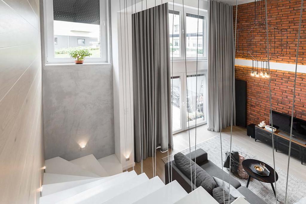 Przytulny loft, widok ze schodów na salon. Projekt Monika Staniec